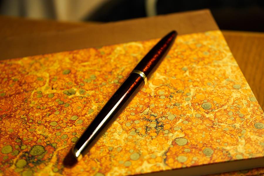 stylo plume sur cahier marbré de papeterie florentine